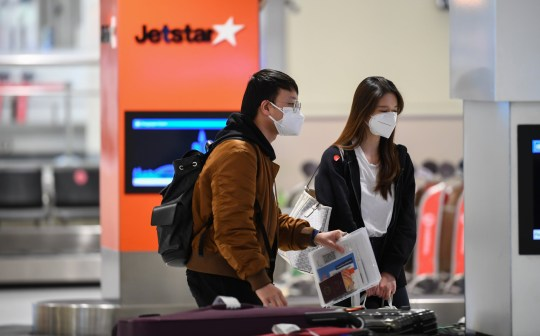 SYDNEY, AUSTRALIA - AUGUST 04: Passengers wearing face masks at Sydney Airport after arriving on a Jetstar flight number JQ510 from Melbourne on August 04, 2020 in Sydney, Australia. NSW Premier Gladys Berejiklian is considering stronger border measures for people travelling into Sydney from Melbourne as coronavirus cases in Victoria continue to rise. At present anyone landing at Sydney Domestic Airport from Melbourne is allowed to catch a taxi or Uber to their approved place of self-isolation. Victoria has reported 11 deaths and 439 new COVID-19 cases in the last 24 hours, while NSW has recorded 12 new cases overnight. (Photo by James D. Morgan/Getty Images) 8591287 - 8591881 8594435