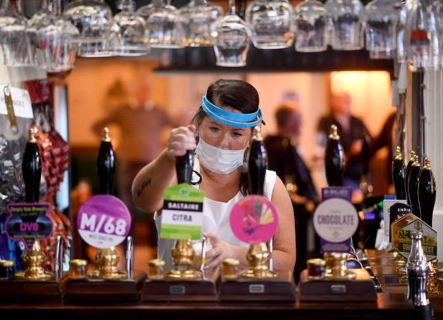 Bar staff wearing a face shield pours a pint.