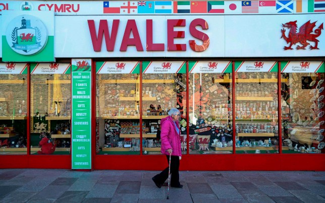 A woman walks past a souvenir shop in Cardiff, south Wales on September 27, 2020, during preparations for the reinstatement of a lock-down, ahead of a 6pm deadline, as new restrictions are introduced to combat the spread of the coronavirus covid-19. - Cardiff will become the first UK capital to go into local lockdown since a national shutdown earlier this year. The new restrictions in Wales, which bar people from entering or leaving areas unless for work, education or another valid reason, will also apply in second city Swansea, from 6pm (1700 GMT) Sunday, and in the town of Llanelli from Saturday. (Photo by Geoff Caddick / AFP) (Photo by GEOFF CADDICK/AFP via Getty Images)