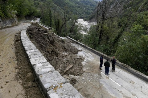 Men stand near a damaged section of road on the outskirts of Roquebilliere, south-eastern France, on October 3, 2020, after the town in the Alpes-Maritimes department was struck by a severe storm. - One person died and authorities listed some 20 as missing after heavy storms lashed southern France and northern Italy with hundreds of aid workers deployed to villages cut off by the deluge. (Photo by NICOLAS TUCAT / AFP) (Photo by NICOLAS TUCAT/AFP via Getty Images)