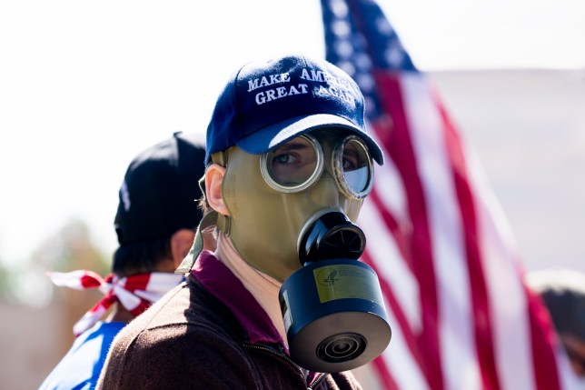 epa08718272 A supporter of US President Donald J. Trump wears a 'Make America Great Again' hat and a gas mask while gathering with Trump supporters wishing him well outside Walter Reed National Military Medical Center, where Trump is receiving treatment after testing positive for Covid, in Bethesda, Maryland, USA, 03 October 2020. White House physician Dr. Sean Conley has said that Trump has not had a fever for 24 hours, has not had trouble breathing and is 'doing very well'. EPA/MICHAEL REYNOLDS
