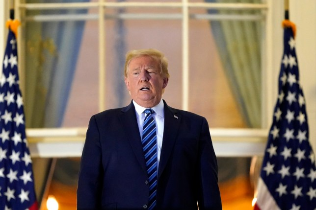 President Donald Trump stands on the balcony outside of the Blue Room as returns to the White House Monday, Oct. 5, 2020, in Washington, after leaving Walter Reed National Military Medical Center, in Bethesda, Md. Trump announced he tested positive for COVID-19 on Oct. 2. (AP Photo/Alex Brandon)