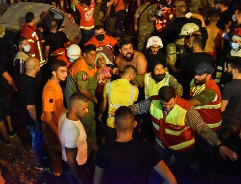 Des membres de la défense civile libanaise et des pompiers évacuent une femme blessée de son appartement après l'explosion d'un réservoir de carburant dans le quartier de Tariq al-Jdide à Beyrouth le 9 octobre 2020. - Une explosion de réservoir de carburant a déclenché un incendie et fait des victimes dans la capitale libanaise Beyrouth, ce qui a déclenché la panique dans une ville déjà ravagée par l'explosion de monstres du mois dernier, ont déclaré les sauveteurs.