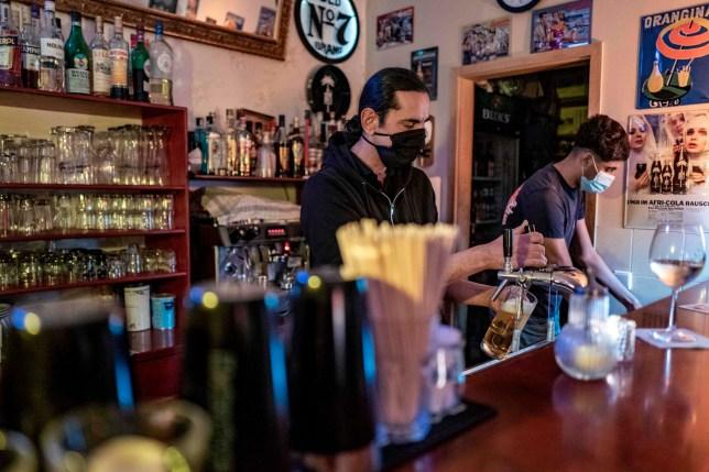 Un barman verse une bière dans un bar du quartier de Prenzlauer Berg à Berlin le 10 octobre 2020. - Stolz, avec d'autres propriétaires de bar à Berlin, a défié les autorités locales sur la réintroduction d'un couvre-feu pour les bars de la capitale, qui sont , à partir du 10 octobre, interdit de circuler entre 23h et 6h.  (Photo par JOHN MACDOUGALL / AFP) (Photo par JOHN MACDOUGALL / AFP via Getty Images)
