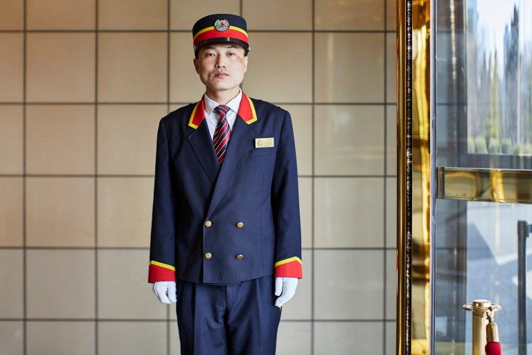 hotels of pyongyang book captures hotel interiors and staff in north korea's capital city: doorman at pothogang hotel