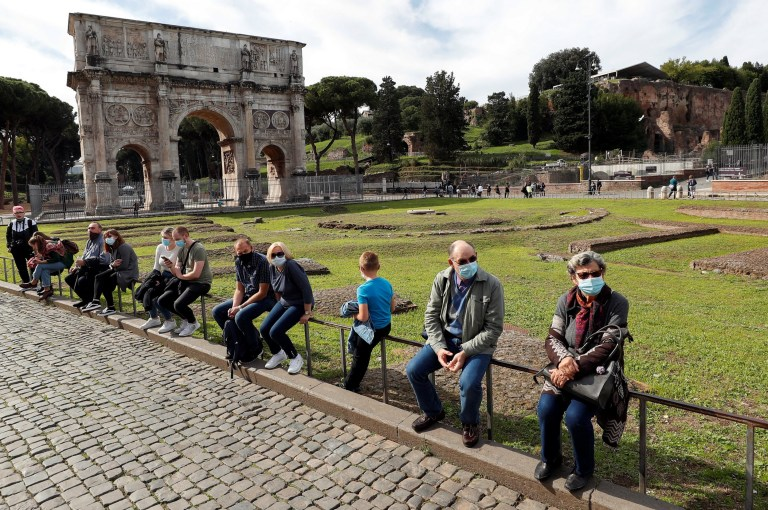 People wearing face masks are seen next to the Arch of Constantine as Italy adopts new restrictions aimed at curbing a surge in the coronavirus disease (COVID-19) infections, in Rome, Italy October 13, 2020. REUTERS/Guglielmo Mangiapane