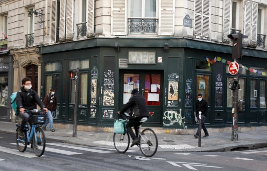 Cyclists ride past the Au Chat Noir bar closed as part of stricter restrictions due to the coronavirus disease (COVID-19) outbreak in Paris, France, October 13, 2020. REUTERS/Charles Platiau