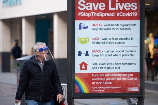 A man wearing a face shield walks past a coronavirus advice sign in Nottingham city centre.