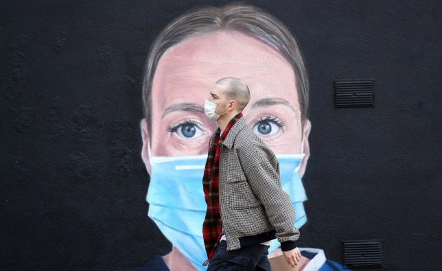 A person wearing a face mask walks past a mural of a nurse in Manchester
