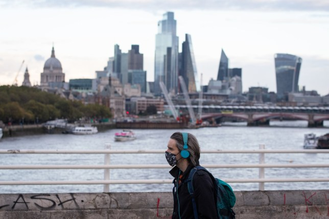 A man wearing a mask walks crosses Waterloo Bridge in London