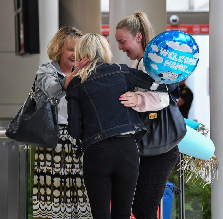 Des amis s'embrassent alors qu'ils se saluent à leur arrivée dans la zone des arrivées internationales de l'aéroport Kingsford Smith de Sydney