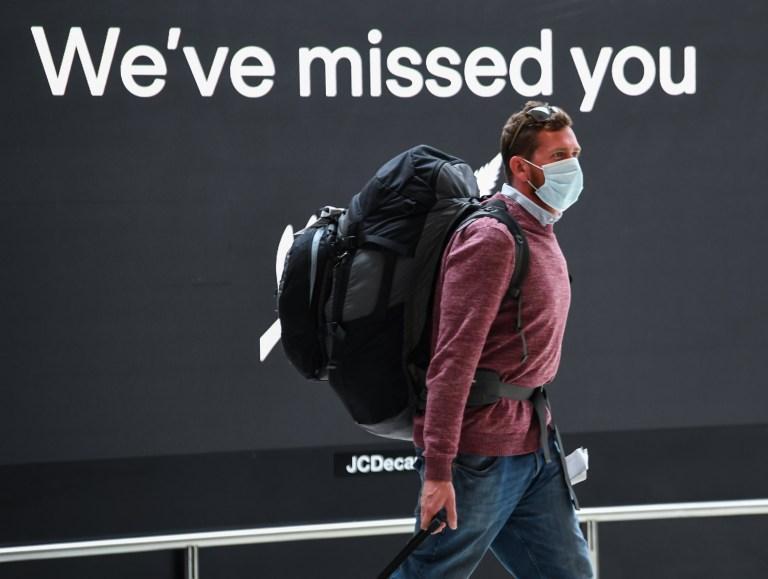 Un passager portant un masque à son arrivée dans la zone des arrivées internationales à l'aéroport Kingsford Smith de Sydney