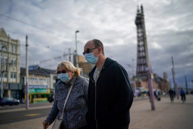A man and a woman wearing face-masks walk past a tower in Blackpool