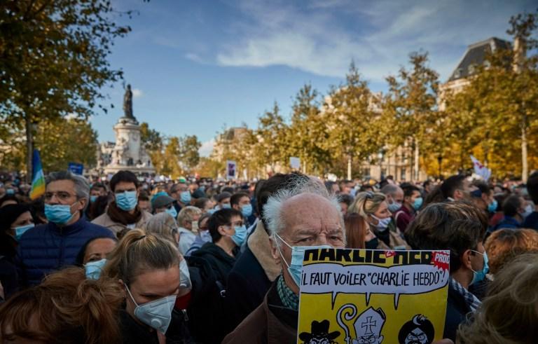 PARIS, FRANCE - 18 OCTOBRE: un manifestant tient une copie du journal satirique Charlie Hebdo lors d'une veillée antiterroriste à la Place de la République pour le professeur assassiné Samuel Paty qui a été tué dans une attaque terroriste dans la banlieue de Paris en octobre 18, 2020 à Paris, France.  Des milliers de personnes ont manifesté leur solidarité et exprimé leur soutien à la liberté d'expression à la suite de l'attaque de vendredi.  La France a ouvert une enquête antiterroriste après l'incident du 16 octobre où la police a abattu l'agresseur de 18 ans qui avait décapité le professeur d'histoire-géographie pour avoir montré une caricature du prophète Mohamed comme exemple de liberté d'expression au Collège Bois d'Aulne école intermédiaire.  (Photo par Kiran Ridley / Getty Images)
