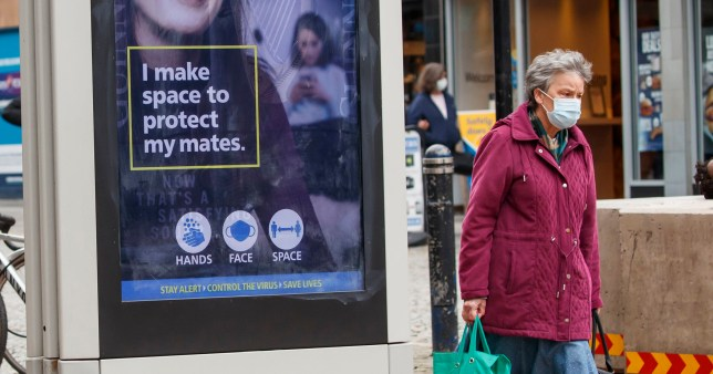 A masked woman carrying her shopping in Sheffield walks past a advertising board giving out advice on coronavirus.