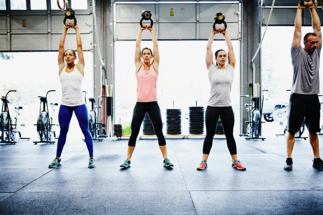 Group of friends training with kettlebells in gym gym