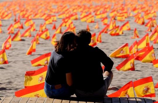 (FICHIERS) Dans cette photo de fichier prise le 4 octobre 2020, un couple est assis à côté de milliers de drapeaux espagnols, représentant les victimes espagnoles du COVID-19, sur la plage de Patacona à Valence.  - L'Espagne a dépassé le million de cas de virus le 21 octobre 2020 selon les chiffres du ministère de la Santé.  (Photo par Jose Jordan / AFP) (Photo par JOSE JORDAN / AFP via Getty Images)