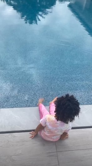 Stormi Webster jumps in the pool with her clothes on