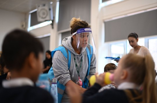 A school worker wearing a face visor due to COVID-19 collects pupils' plates after they had cooked hot dinners in the canteen, during their lunch break at St Luke's Church of England Primary School in East London on September 3, 2020.