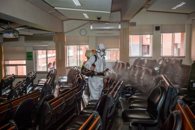 A health worker dressed in a protective suit sprays disinfectants as a preventive measure against the spread of Coronavirus (COVID-19) at the National Taiwan Normal University.