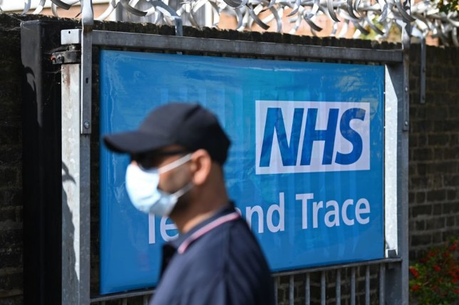 A worker wearing a face mask or covering due to the COVID-19 pandemic, stands near a sign for Britain's NHS (National Health Service) Test and Trace service, as he works at the entrance to a novel coronavirus walk-in testing centre in East Ham in east London