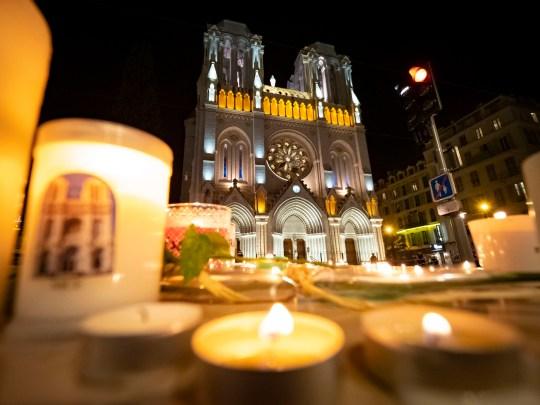 Les gens rendent hommage la nuit devant la basilique Notre-Dame le 29 octobre 2020 à Nice, France.
