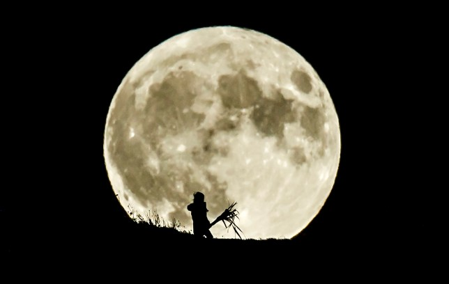 A person watches the Blue Moon rise over Castle Hill in Huddersfield, it will be the last full moon to fall on Halloween until 2039. PA Photo. Picture date: Saturday October 31, 2020. A Blue Moon is the second full moon in a calendar month ? but can also be defined as the fourth full moon in an astronomical quarter. The next full moon to fall on Halloween will be October 31, 2039. Photo credit should read: Danny Lawson/PA Wire