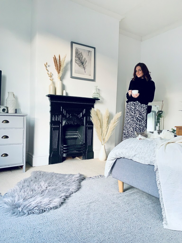 What I Rent: Vikki, £625 for a two-bedroom flat in Derby - vikki standing in her bedroom, with grey bedding, rug, and fireplace, plus chester the kitten
