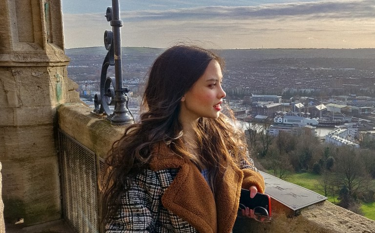 Picture of Samantha Kilford outside, standing by a wall and looking out across the landscape
