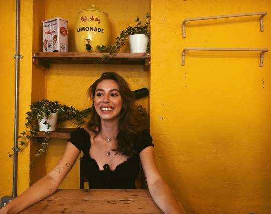 Elizabeth McCafferty sat at a table, smiling, in front of a yellow painted interior