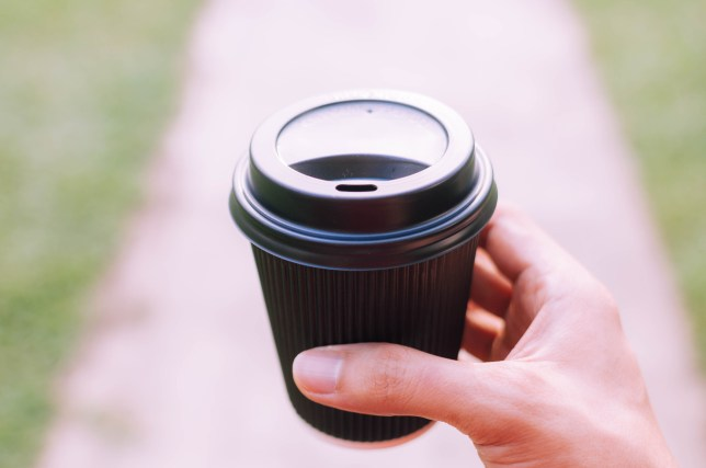 A young person is holding a disposable cup of coffee on a walkway