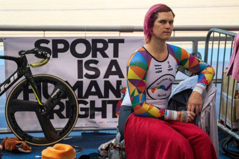 Transgender cyclist Rachel McKinnon sitting in front of her bike and a banner that reads 'sport is a human right'