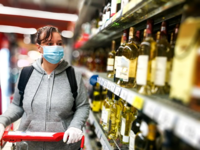 Woman wearing protective face mask and gloves shopping for alcohol in supermarket.