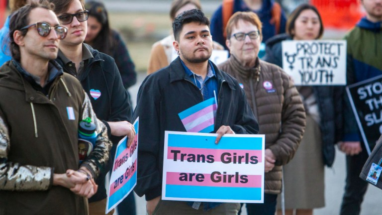 Person with placard that reads 'Trans Girls are Girls' as part of a protest against Iaho's bill to ban transgender women and girls from female sports