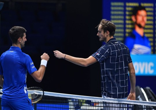 Russia's Daniil Medvedev (R) bumps fists with Serbia's Novak Djokovic after winning the match in two sets during their men's singles round-robin match on day four of the ATP World Tour Finals tennis tournament at the O2 Arena in London on November 18, 2020.