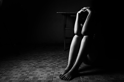 a black and white image of a distressed woman sitting on ground with her head bent down and her arms over it.