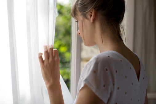 a woman in a white top  is looking out of a window