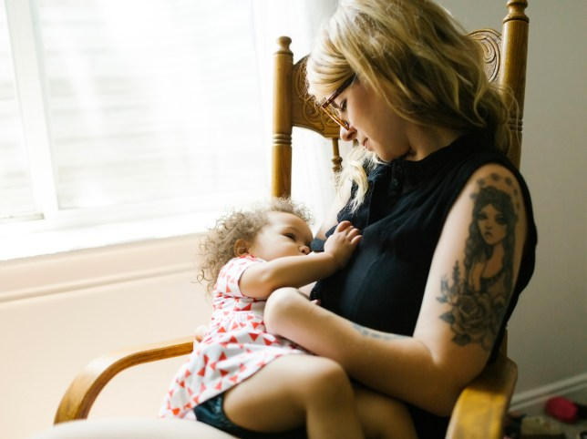 Mother sitting on chair and breastfeeding daughter
