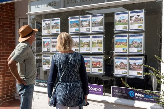 Couple looking in an estate agent's window at properties for sale.