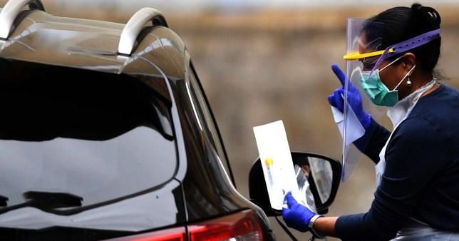 Woman wearing a face mask and visor at a drive-through coronavirus testing site