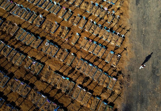 TOPSHOT - Aerial view showing a man walking past graves in the Nossa Senhora Aparecida cemetery in Manaus on June 21, 2020. - The novel coronavirus has killed at least 464,423 people worldwide since the outbreak began in China last December, being Brazil Latin America's worst hit country with 49,976 deaths from 1,067,579 cases. (Photo by MICHAEL DANTAS / AFP) (Photo by MICHAEL DANTAS/AFP via Getty Images)
