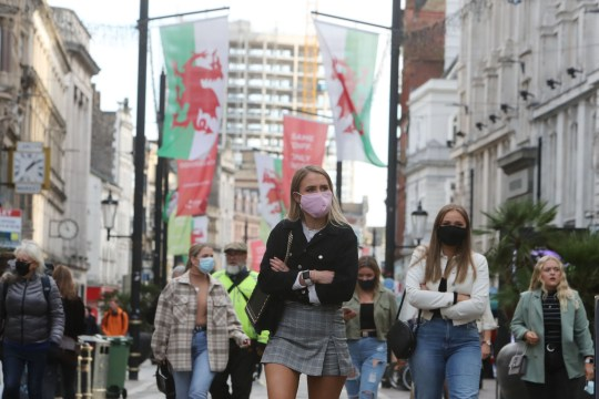 People wearing masks because of the coronavirus pandemic are seen in the centre of Cardiff on October 23, 2020, hours before Wales goes into a two-week lockdown.