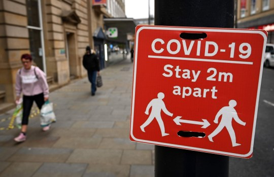 Shoppers walk past a sign displaying COVID-19 guidelines, in Bradford, west Yorkshire on October 31, 2020, as the number of cases of the novel coronavirus COVID-19 rises. - British Prime Minister Boris Johnson is considering imposing a new lockdown across England within days following warnings his localised restrictions strategy has failed to curb soaring coronavirus rates, reports said Saturday. (Photo by Paul ELLIS / AFP) (Photo by PAUL ELLIS/AFP via Getty Images)