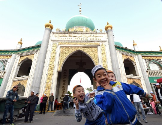 A group of Chinese Muslim orphans pose outside the Nan Guan mosque during the sacrificial Eid al-Adha festival in Yinchuan, northern China's Ningxia province on September 24, 2015. Muslims across the world celebrate the annual festival of Eid al-Adha, or the Festival of Sacrifice, which marks the end of the Hajj pilgrimage to Mecca and in commemoration of Prophet Abraham's readiness to sacrifice his son to show obedience to God. AFP PHOTO / GOH CHAI HIN (Photo credit should read GOH CHAI HIN/AFP via Getty Images)