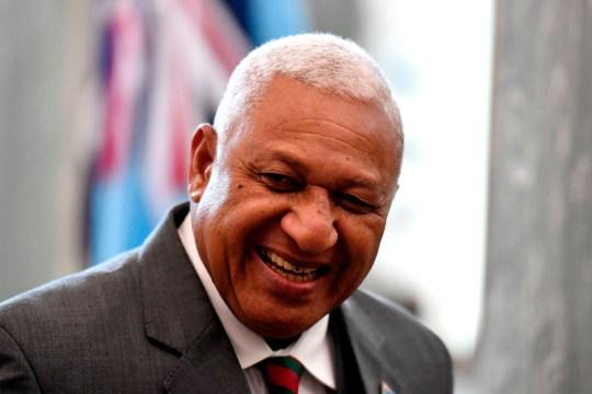 Fiji Prime Minister Frank Bainimarama smiles after signing a visitors book at Parliament House in Canberra on September 16, 2019. - Bainimarama arrived in Australia for five days of meetings with members of the Fijian community in Sydney and Canberra, as well as a bilateral meeting with Morrison where they are expected to talk trade and investment. (Photo by MICK TSIKAS / POOL / AFP) (Photo credit should read MICK TSIKAS/AFP via Getty Images)