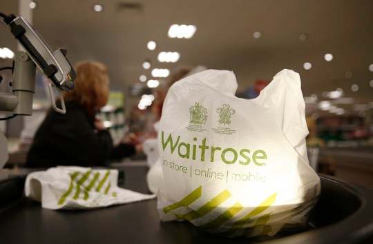 A plastic carrier bag sits beside a card payment device at the check-out counter inside a Waitrose Ltd. supermarket in the Hove district of Brighton, U.K., on Tuesday, Jan. 27, 2015. Britain has outperformed its neighbors, with the fastest economic growth in the Group of Seven industrialized nations. Photographer: Simon Dawson/Bloomberg via Getty Images
