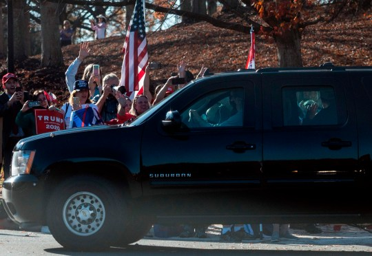US President Donald Trump(R) looks out of his car as he drives past supporters outside of the Trump International Golf Club in Sterling, Virginia on November 8, 2020. - Donald Trump returned Sunday to his golf course in a Washington suburb, a day after news media announced his defeat in the presidential election at the hands of Democrat Joe Biden. For his part, the former vice president attended Mass along with family members at a Catholic church near his home in Wilmington, Delaware, as he regularly does. (Photo by ANDREW CABALLERO-REYNOLDS / AFP) (Photo by ANDREW CABALLERO-REYNOLDS/AFP via Getty Images)