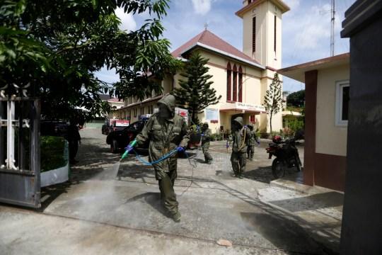 epa08809079 Des policiers de l'unité spéciale de police (BRIMOB) pulvérisent du liquide désinfectant dans une église catholique pour empêcher la propagation du coronavirus à Banda Aceh, Indonésie, le 9 novembre 2020. EPA / HOTLI SIMANJUNTAK