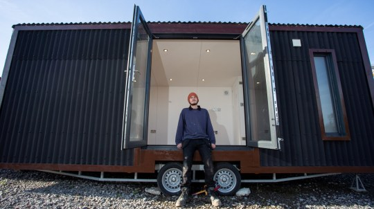 George Rose spent the first coronavirus lockdown building a house worth ??20,000 out of a trailer. He started the project after he was forced to find somewhere else to live. He has now found accommodation and is raffling off the tiny home. Bristol. 11 November 2020. See SWNS story SWBRtiny. A man who built Britain's smallest home is raffling it for ??3 a ticket - and it comes on wheels so can be moved anywhere. George Rose was forced to find somewhere else to live during lockdown so decided to undertake his ??20,000 project. He used his skills as a qualified builder to refurbish a trailer he had bought, which measures just 6.6m by 2.55m. George, 29, has now found somewhere else to live so decided to sell the tiny home - which is so small is does not need planning permission.