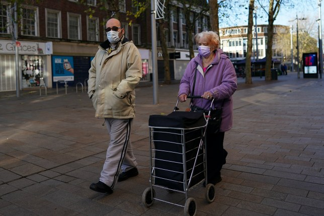 an elderly couple wearing face masks in hull
